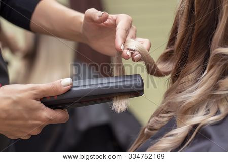 Professional Hairdresser Curling A Hair Strand Of A Model With Relaxed Hair In A Beauty Salon. Conce