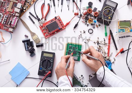 Faceless Portrait Of Radioman Testing Electric Current In Circuit Board Of Disassembled Laptop Using