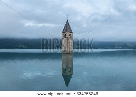 Church Tower Of Altgraun, Reschensee (south Tyrol, Italy) On A Cloudy Morning In Summer
