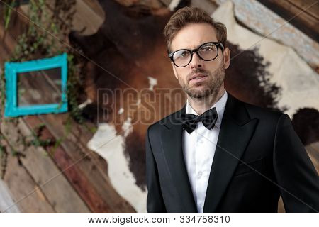Bothered fashion model looking away while wearing tuxedo and glasses, sitting on a table on coffeeshop background