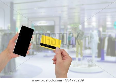 Man Holding Credit Card In Hand And Entering Security Code Using Mobile Phone. Black Friday, Sale