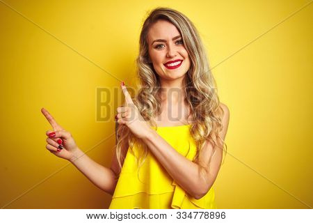 Young attactive woman wearing t-shirt standing over yellow isolated background smiling and looking at the camera pointing with two hands and fingers to the side.