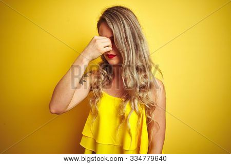 Young attactive woman wearing t-shirt standing over yellow isolated background tired rubbing nose and eyes feeling fatigue and headache. Stress and frustration concept.
