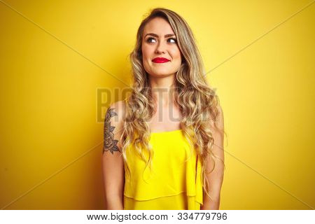 Young attactive woman wearing t-shirt standing over yellow isolated background smiling looking to the side and staring away thinking.