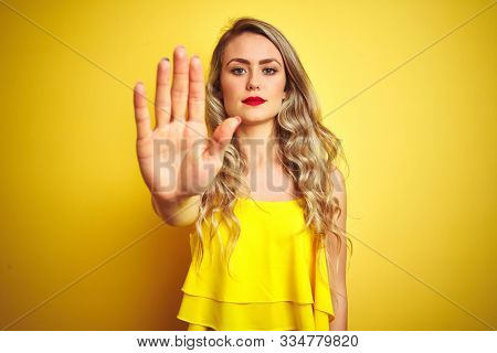 Young attactive woman wearing t-shirt standing over yellow isolated background doing stop sing with palm of the hand. Warning expression with negative and serious gesture on the face.
