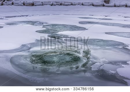 Holes In Ice, Covering Aerated Fish Pond During Winter Season. Ice Is Melting, Because Of Aeration P