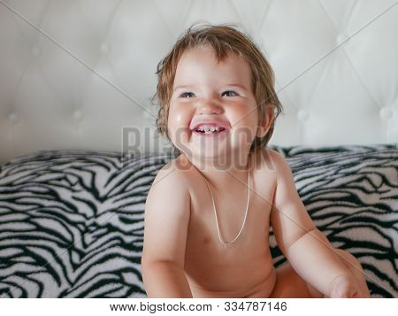 The Naked Baby Is Laughing. Laugh In All Your Teeth. Happy Laughing Baby. White Teeth Of A Newborn B