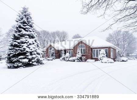 Tidy brick home after a winter snowfall.