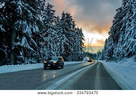 The Icy Winter Road To The Ski Slopes Of Seymour Mountains Passes Through A Snowy Forest, Cars And A