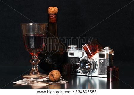 nostalgia still life with an old-fashioned camera brown bottle of alcohol rare photos and walnut poster