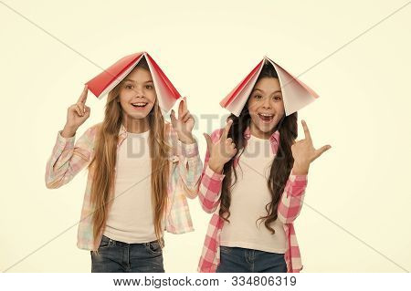 Knowledge Is Power. Adorable Little School Girls Holding Books Over Heads Full Of Knowledge. Septemb