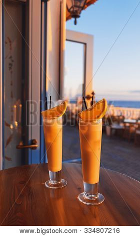 Two tropical cocktails adorned by fresh orange and brightly lit by setting sun on the wooden table of a seafront mediterranean cafe. Copy space. poster