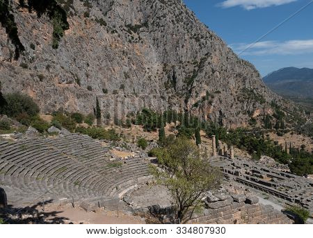 View Of Amphitheater And Temple Of Apollo, The Site Of The Oracle Of Delphi, With Mountains And The