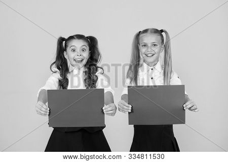 Promote With Advertising. Happy Small Children Showing Pink Paper Sheets For Advertising On Yellow B