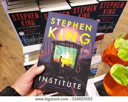 Montreal, Canada - October 23, 2019: A Hand Holding A Stephen King Book The Institute Over A Shelf W