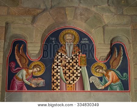 Meteora, Greece - September 23, 2019: Close Up Of A Mural With A Saint Holding A Bible And Two Angel