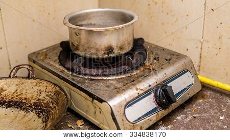 An Old Burned Stainless Steel Pot On A Stove. Oily, Messy And Greasy Kitchen. Dirty Oil Stain Around