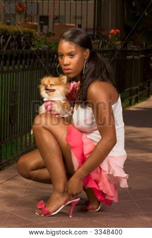 Black Woman Squatting, With Pomeranian Spitz Dog