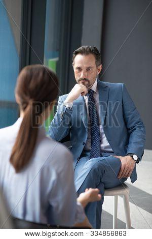 Serious Affluent Businessman Listening To Journalist Asking Him Questions