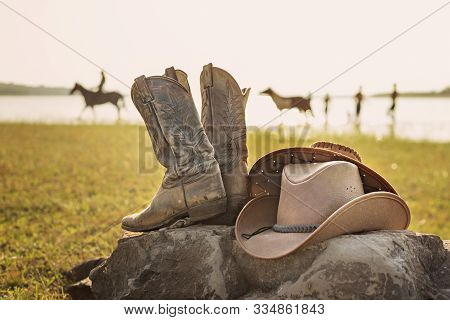 Wild West Retro Cowboy Hat And Pair Of Old Leather Boots On The Rock