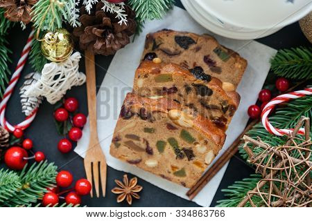 Sweet Christmas Fruit Cake Slices On White Paper Put On Black Granite Table In Top View Flat Lay Wit