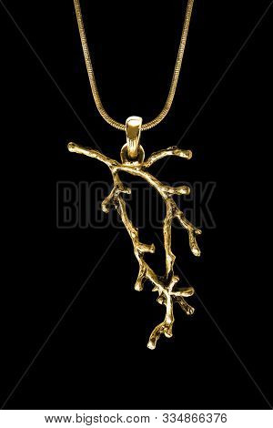 Gold Pendant In The Shape Of Tree Branch Hanging On A Chain On Black Background