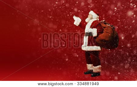 Full length portrait of the good old Santa Claus with a bag of gifts under a snowfall on a red background. Merry Christmas and Happy New Year! Copy space.