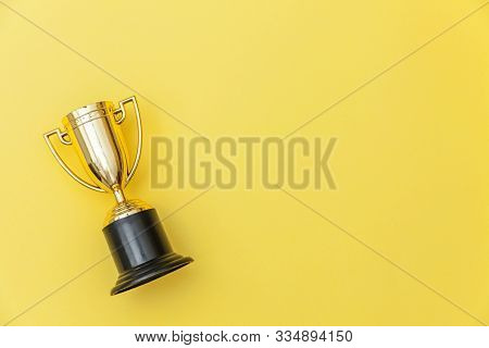 Simply Flat Lay Design Winner Or Champion Gold Trophy Cup Isolated On Yellow Colorful Background. Vi