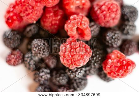 Fresh Berries Of Sweet Red And Black Raspberries On A White Background.