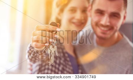 Happy couple with keys for house or apartment after buying real estate