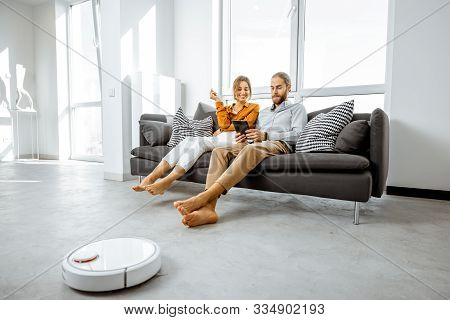 Young Couple Relaxing On The Couch While Automatic Vacuum Cleaner Doing The Housework In The Modern