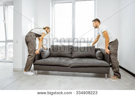 Two Professional Movers In Workwear Placing Large Couch In The Living Room Of The Modern White Apart