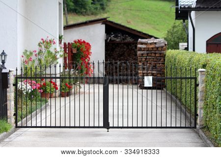 Suburban Family House Paved Driveway Closed With Dark Wrought Iron Doors Mounted On Stone Tiles Cove