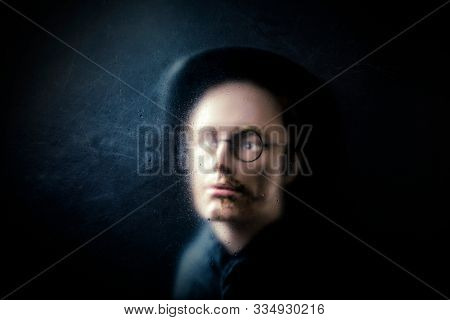Mystery figure with hat and glasses behind a dusty scratched glass.