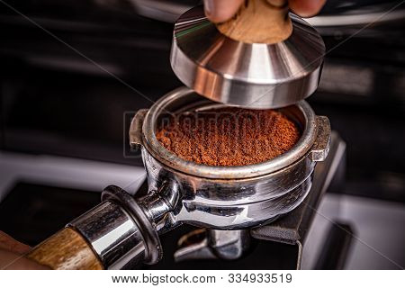 Barista Is Using A Tamper To Press Freshly Ground Morning Coffee