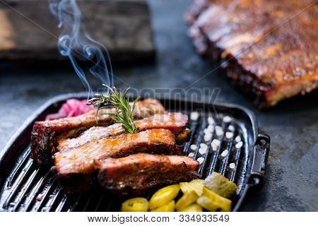Grill Restaurant Menu. Closeup Of Smoked Pork Ribs, Served In Griddle Pan And Decorated With Burning
