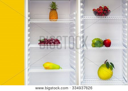 In The Open Refrigerator On The Shelves Are Artificial Fruits, Multicolor Plastic Food In The Refrig