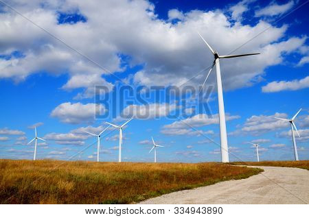 Green Renewable Energy Concept - Wind Generator Turbines In Field Blue Sky. Wind Green Environment E