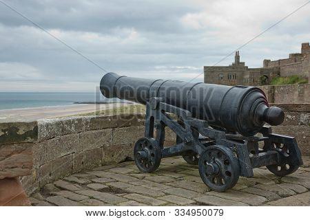 Old Iron Cannon At Bamburgh Castle On Northumberland Coast Of England, Uk