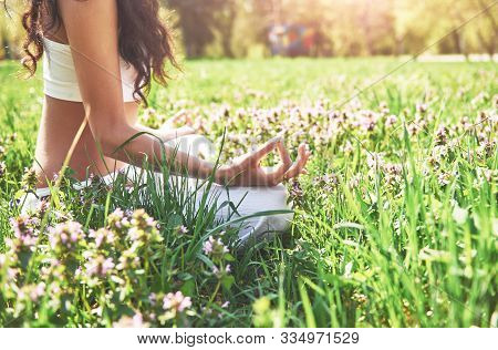 Yoga Meditation In A Park On The Grass Is A Healthy Woman At Rest.