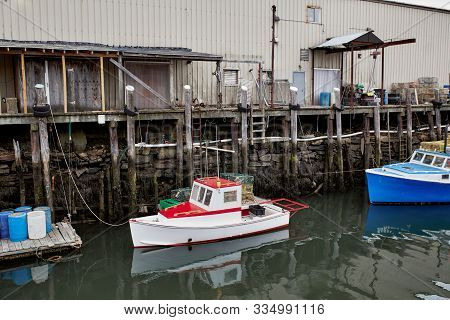 Commercial Fishing Wharf With Stacks Of Lobster Traps In The Old Port Harbor District Of Portland, M