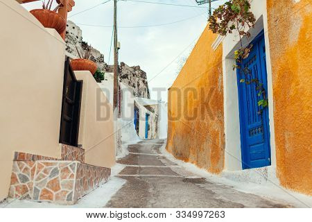 Old Street In Akrotiri Village On Santorini Island, Greece. View Of Castle And Blue Doors. Tradition