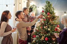Young man with his little daughter decorating Christmas tree at home among other family members while preparing for holiday