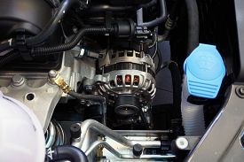 New Car Alternator, Close-up View. An Alternator Installed In The Engine Compartment Of A Modern Car