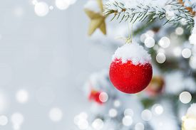 Christmas Tree In Snow Background. New Year Composition With Fir Tree, Balls And Lights And Bokeh. C