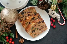 Sweet Christmas Fruit Cake Slices On White Plate Put On Black Granite Table In Top View Flat Lay Wit