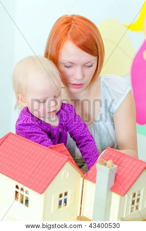 Child And Their Mother Playing With Dollhouse