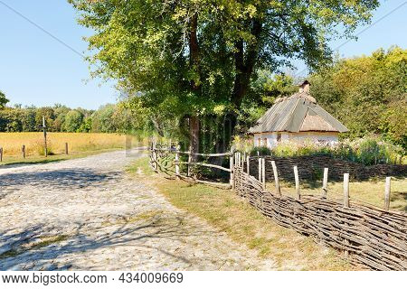 Summer Landscape Of An Antique Ukrainian Rural Street With A Wicker Wooden Fence And A Rural Hut.