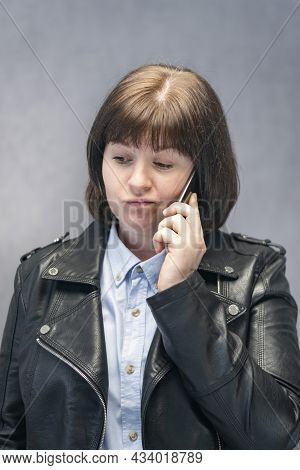 Young Woman In Strict Shirt And Leather Jacket Is Talking On Cell Phone. Indignant Boss. Vertical Fr