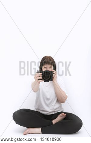 Woman Photographer With Camera In Hands Talks Sitting In Lotus Position And Talking On Phone. Multit